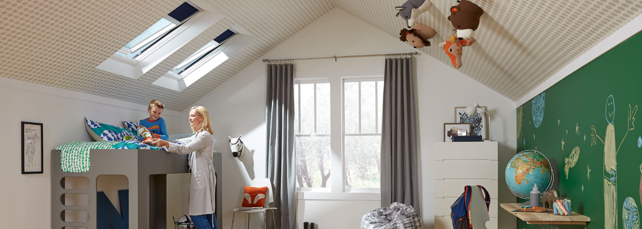 A mom and son reading in his room brighten with daylight from VELUX Solar  Powered Fresh