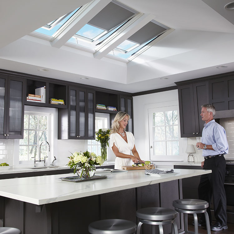 A couple cooking in their kitchen with VELUX Solar