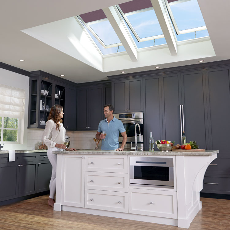A couple enjoying wine in their kitchen with VELUX Solar