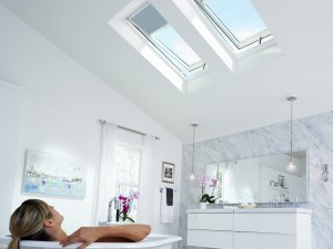 woman in bathtub looking up skylights that have the blinds slightly down in sydney