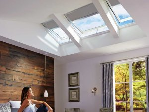 woman in bedroom looking up at skylights with blinds in auckland