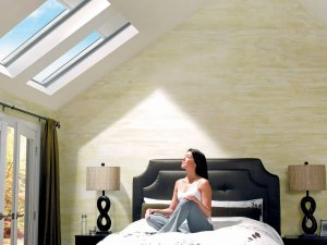 woman in bedroom admiring natural daylight through skylights in auckland