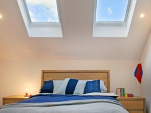 skylights above bed with blue and white sheets in auckland
