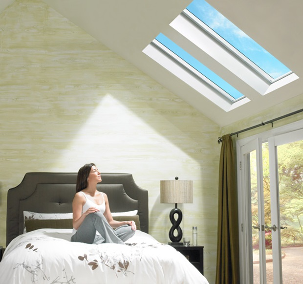 Woman Enjoying The Sunlight In Her Bedroom With Velux Fixed Skylights