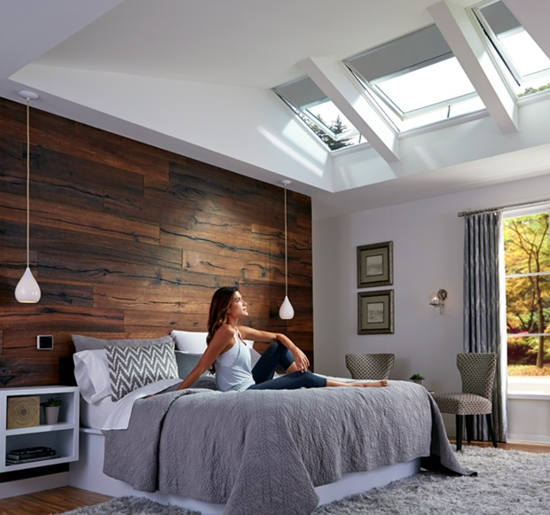 Woman Enjoying Daylight And Fresh Air In Her Bedroom With Velux Solar